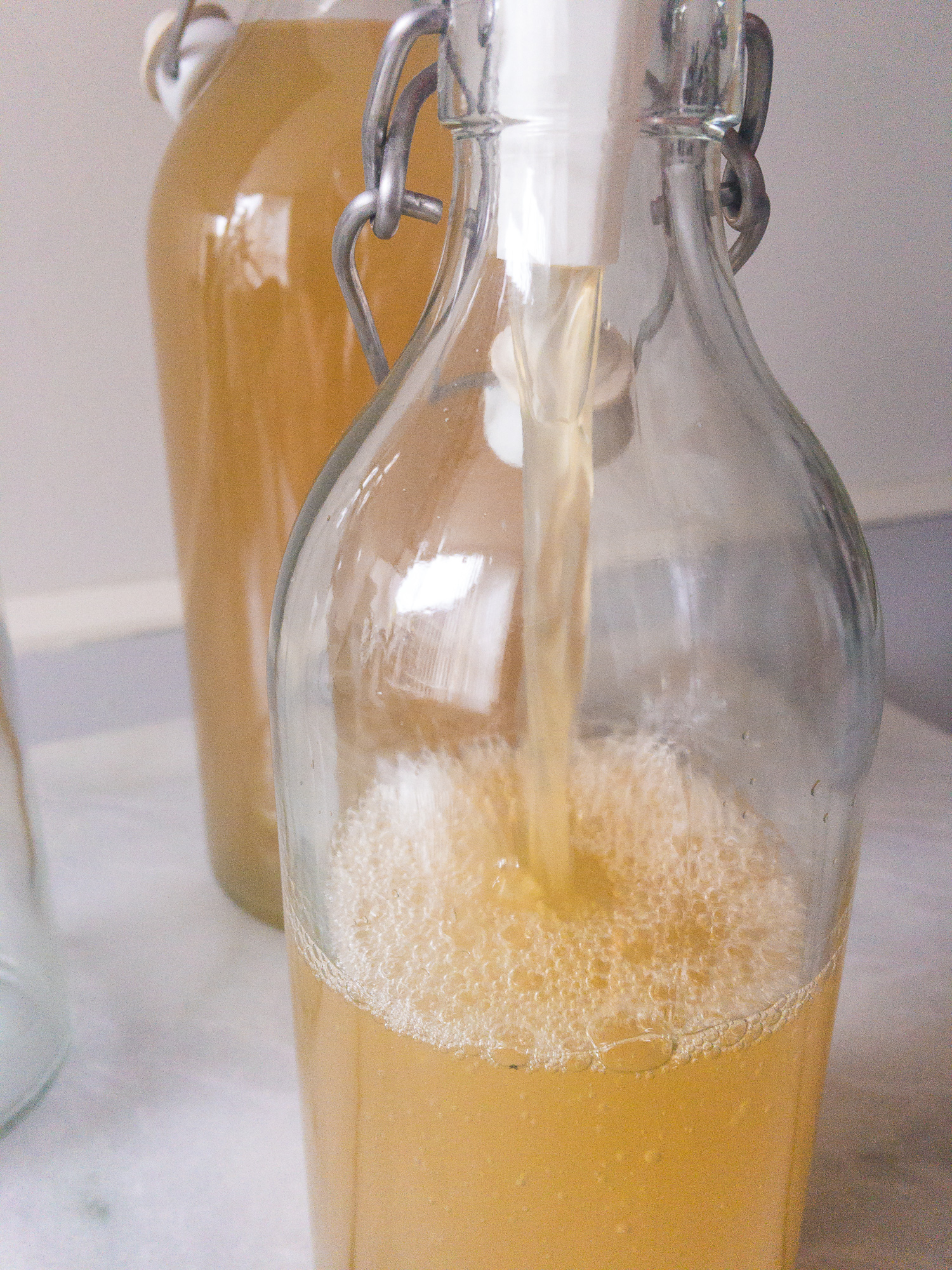 pouring elderflower cordial in bottles